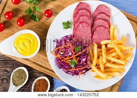 french fries and sliced smoked veal with cabbage salad on white plate on cutting board with mustard in gravy boat and spices on porcelain spoons view from above