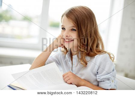 education, people, children and learning concept - happy student girl reading book at school