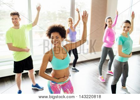 fitness, sport, dance and lifestyle concept - group of smiling people with coach dancing in gym or studio