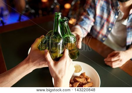 people, men, leisure, friendship and celebration concept - close up of male friends drinking beer and clinking bottles at bar or pub
