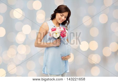 pregnancy, motherhood, holidays, people and expectation concept - happy pregnant woman with flowers touching her big belly over holidays lights background