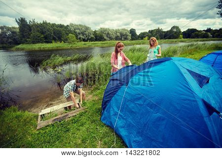 camping, travel, tourism, hike and people concept - group of smiling friends setting up tent outdoors