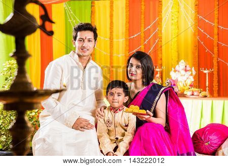 smart looking indian young couple in traditional wear sitting on sofa with boy child and ganesh idol or ganpati bappa in the background on ganesh festival or ganapati festival or utsav day