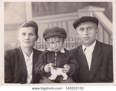 KALININ, RUSSIA - CIRCA 1961: Family portrait of young man, woman and child with toy in his hands (vintage photo from family archive)