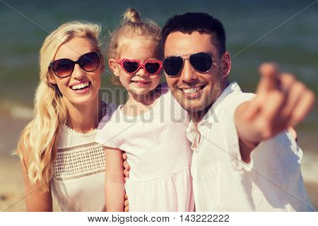 travel, vacation, adoption and people concept - happy family with little girl in sunglasses pointing finger on summer beach