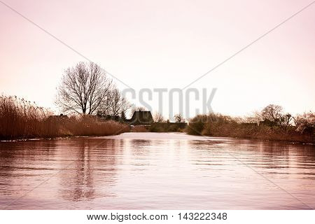 River scene after sunset with bare trees and village in the background. Winter scene.