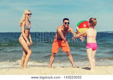 family, summer vacation, adoption and people concept - close up of happy man, woman and little girl playing with inflatable ball on beach