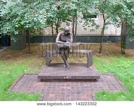 Moscow, Russia - July 07, 2016: Bronze sculpture of a student sitting at his desk in patio of the Moscow State Linguistic University