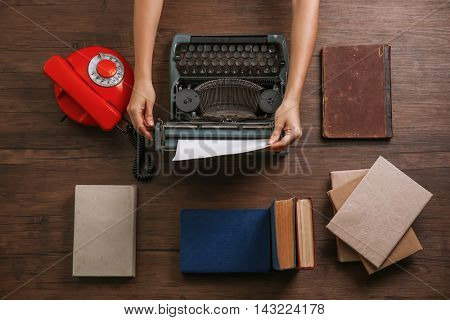 Woman hands working with retro typewriter, books and phone on wooden background