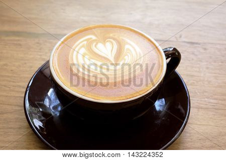 Latte coffee and latte art on wood background