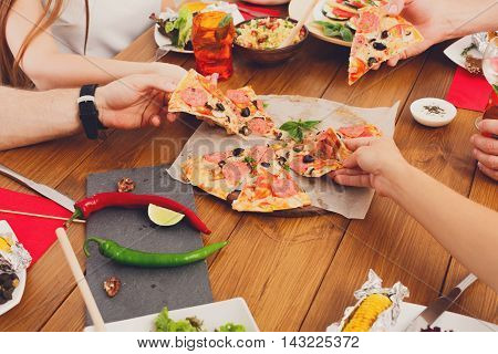 People eat pizza at festive table served for party. Friends celebrate with catering food on wooden table closeup. Woman and man's hands take the pieces of italian pizza. Unrecognizable people