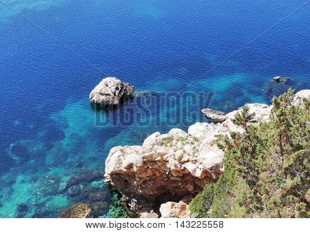 Rocky coastline background with blue sea and copy space.