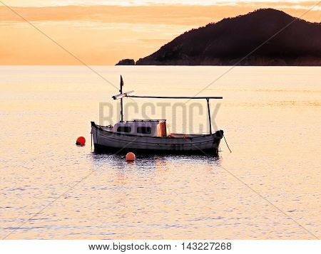 Idyllic sunset scene with fisher boat and seascape.