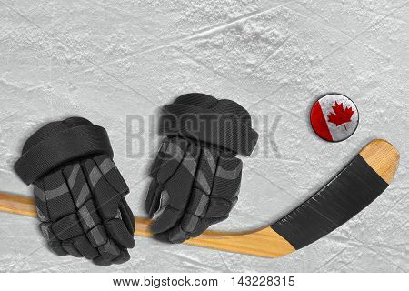 Hockey puck stick and gloves on the ice arena. Concept