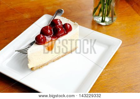 Cherry cheesecake in white plate on wood table