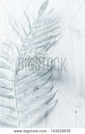 Silver fern leaf and a glass ornament on a white wooden surface