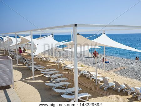 A beautiful beach city with sun loungers. Tourists relax and bathe in crystal clear water of sea.