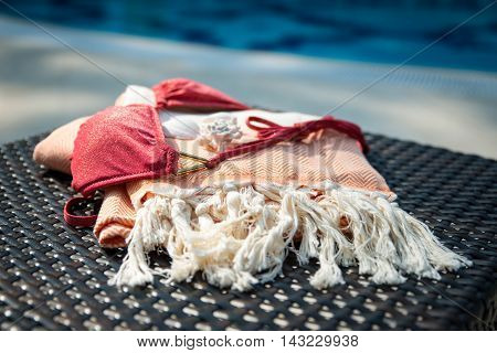 Concept of summer accessories close-up of white and orange Turkish towel, bikini top and white seashells on rattan lounger with blue swimming pool as background.
