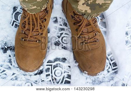 pair of legs in brown military boots