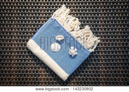 Concept of flat lay white and blue Turkish towel on rattan lounger.