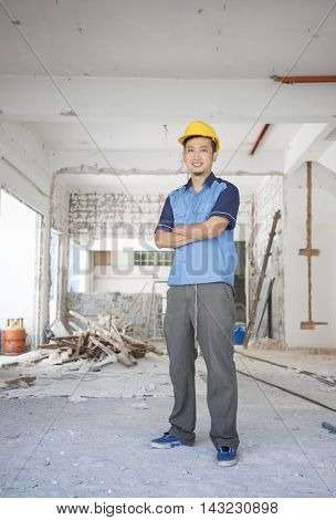 Asian construction worker with hardhat standing at site.