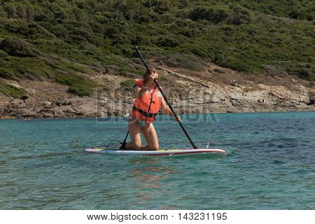 Kid Paddle Surf Surfer Girl With Row In Mediterranean Beach