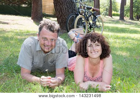 Happy Couple Lying On Grass With Bike In The Background