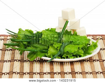 Green lettuce rolls with cubes of cheese on a straw mat over white background