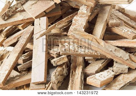 Stack of brown parquet damaged by termites place on white background.
