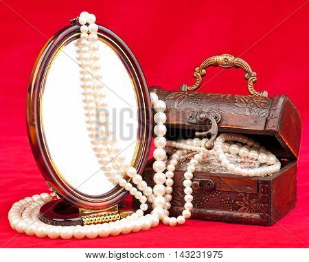 Jewel box with pearl necklace over red background
