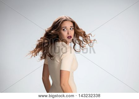 The young woman's portrait with frightened emotions on gray background