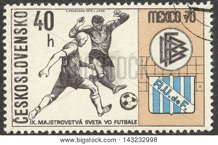 MOSCOW RUSSIA - CIRCA JUNE 2016: a post stamp printed in CZECHOSLOVAKIA shows Two Players and Badges of Germany and Uruguay the series