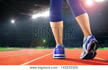 Legs of athlete on running track in the stadium