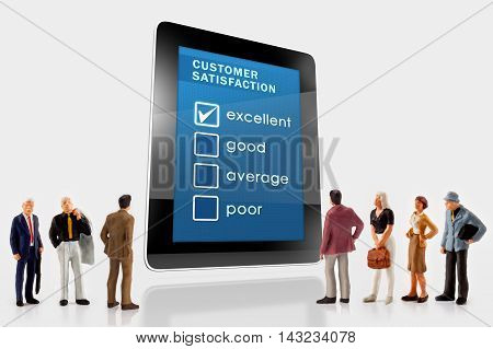 Online customer survey on a digital tablet, with a group of miniature people in front
