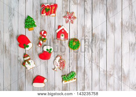 Christmas colorful gingerbread cookies on white wooden background. Winter holidays concept. Space for text.