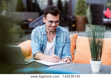 Put it down. Cheerful smiling young woman sitting at the table and making notes while resting in the cafe