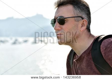Handsome man over sea view. Outdoor male portrait. Trip, vacation, holiday, tourism, leisure, lifestile, summer time concept, image toned and noise added