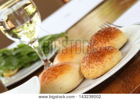 Butter and fresh bread rolls on a plate next to a glass of water