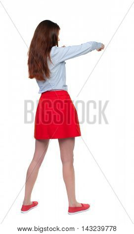 skinny woman funny fights waving his arms and legs. Isolated over white background. Long-haired brunette in red skirt has a hand.