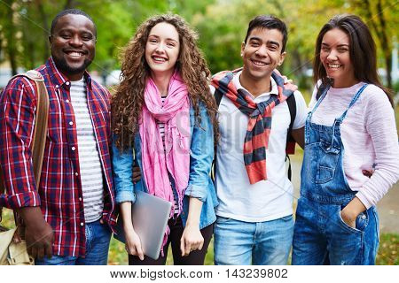 Portrait of happy college students standing together outdoors