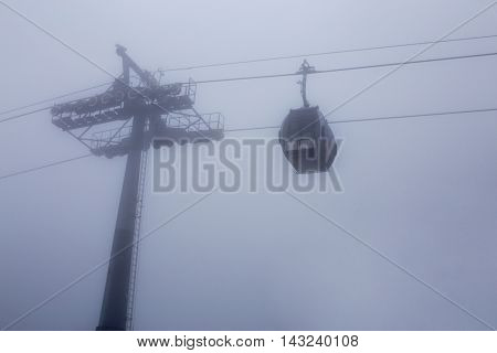 cable way with cabin car in deep mist on white background