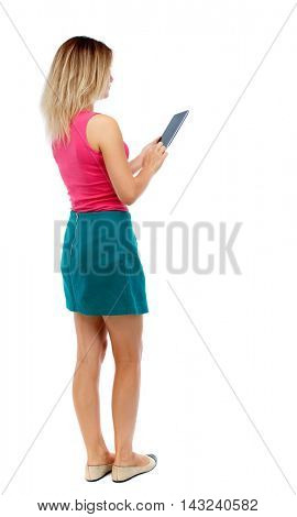 back view of standing young beautiful  woman using a mobile phone or tablet computer. girl  watching. Rear view people collection.  backside view of person.  Isolated over white background. Blonde in