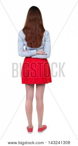 back view of standing young beautiful  woman.  girl  watching. Rear view people collection.  backside view of person. Long-haired brunette in red skirt standing with his hands behind his back.