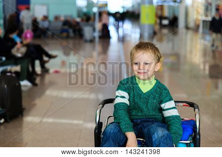 little boy at airport riding on luggage cart, kids travel