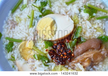 rice porridge topping brown egg and dressing fried chili paste