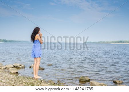 Sad Young Brunette Woman In A Blue Summer Dress Standing On The River Bank