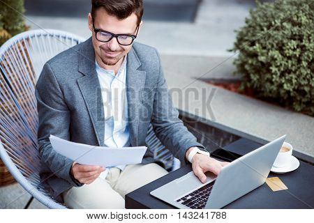 Involved in work. Delighted handsome businessman sitting at the table and working with papers while using laptop