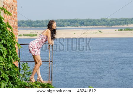 Young Brunette Girl Is Standing On The Balcony Of The Old Against The Backdrop Of The River And Look