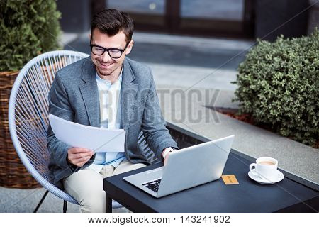 Work with inspiration. Cheerful handsome smiling businessman sitting at the table and working with papers while using laptop