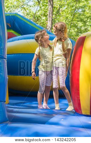 Two Girls Grimacing Happily Looking At Each Other By Jumping On An Inflatable Trampoline